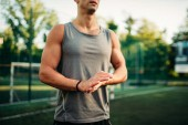 Muscular male athlete on training, fitness workout. Strong sportsman in park