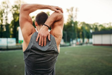 Photo for Muscular male athlete doing stretching exercise, back view, fitness workout. Strong sportsman in park - Royalty Free Image