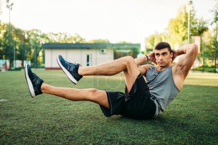 Male athlete doing abs exercises on outdoor fitness workout. Strong sportsman on sport training in park