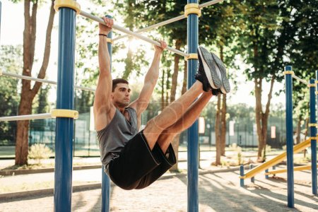 Athletic man doing abs exercise  using horizontal bar, outdoor fitness workout. Strong sportsman on sport training in park
