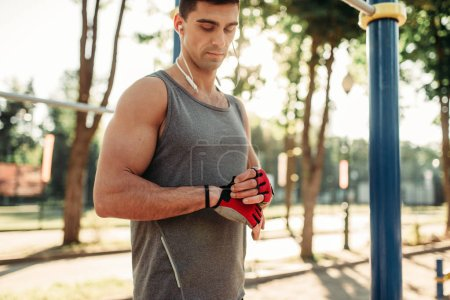 Male athlete in headphones poses, outdoor fitness workout. Strong sportsman on sport training in park