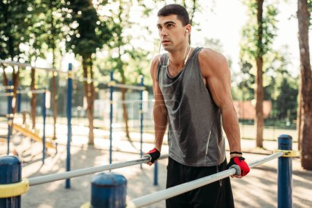 Male athlete in headphones exercises on parallel bars, outdoor fitness workout. Strong sportsman on sport training in park