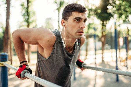 Male athlete in earphones exercises on parallel bars, outdoor fitness workout. Strong sportsman on sport training in park