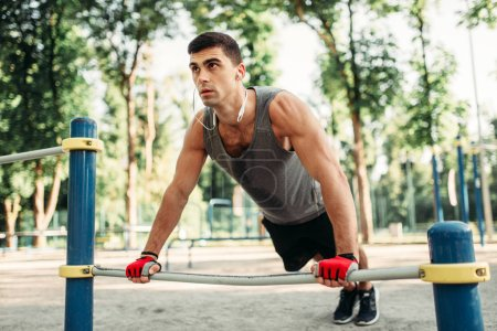 Athletic man doing push-up exercise using horizontal bar, outdoor fitness workout. Strong sportsman on sport training in park