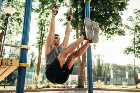 Athletic man doing exercise using horizontal bar, outdoor fitness workout. Strong sportsman on sport training in park