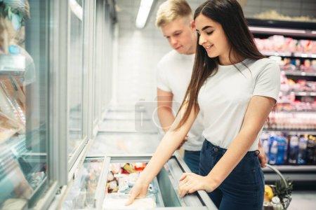 Photo pour Jeune couple choisissant des produits surgelés au supermarché. Clients en magasin alimentaire - image libre de droit