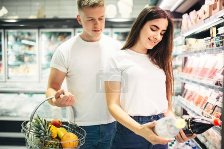 Photo for Young couple choosing products in supermarket. Customers in food store, family in grocery - Royalty Free Image