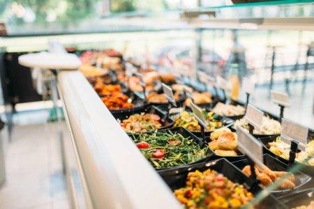 Frais, cuits aliments en magasin, personne. Vitrine avec salades préparées et viande produits en marché