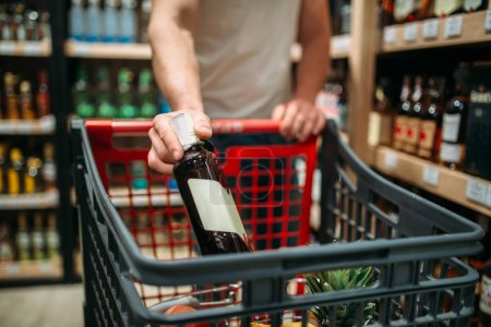 Male person put bottle of wine in a cart, alcohol section in market. Shelves with drinks on background