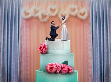 Wedding cake with bride and groom statuettes on the top. Bridal pie for newlyweds with little figurines, traditional celebration ceremony symbol
