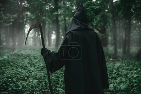 Death in a black hoodie and with a scythe in the dark misty forest. Horror style, fear, spooky demon