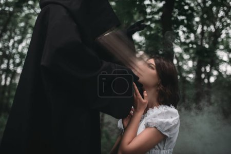 Death in a black hoodie takes the soul of young female victim, forest on background. Photo in horror style, mystery ritual