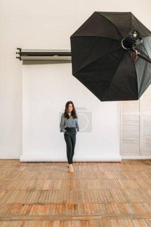 Photo pour Beau modèle pose en fond de studio, blanc photographique, matériel d'éclairage. Femme attirante sur studio shot - image libre de droit