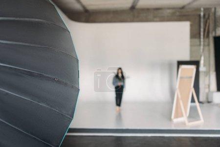 Photo pour Matériel d'éclairage professionnel en studio photo, jeune femme pose sur fond blanc. Modèle attrayant sur studio shot - image libre de droit