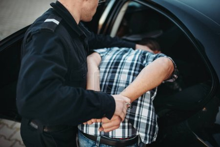 Police officer put the intruder into the car. Cop at the work. Law protection concept, professional safety control