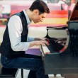 Male pianist practicing composition on grand piano...