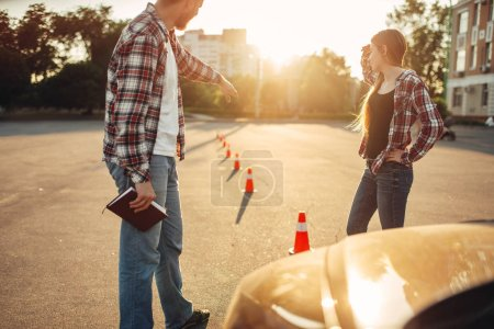 Photo for Male instructor and woman student on lesson for novice car drivers, driving school concept. Test for beginner - Royalty Free Image