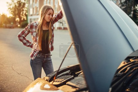 Photo pour Concept de panne de voiture, femme debout contre le capot ouvert sur le bord de la route. Une conductrice regarde le moteur cassé du véhicule - image libre de droit