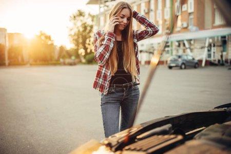 Photo pour Concept de panne de voiture, femme triste contre capot ouvert sur le bord de la route. Une conductrice regarde le moteur cassé du véhicule - image libre de droit