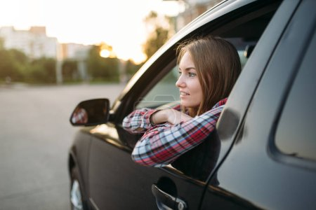 Photo for Smiling female driver beginner looks out of the car window. Woman in vehicle, driving automobile concept - Royalty Free Image