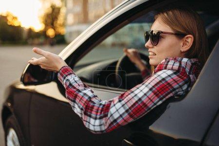Photo for Female car driver in sunglasses, boorish behavior.  Woman in vehicle, aggressive automobile driving concept - Royalty Free Image