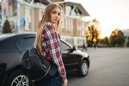 Photo for Young woman driver with travel bag against a car. Female person and vehicle, automobile driving concept - Royalty Free Image