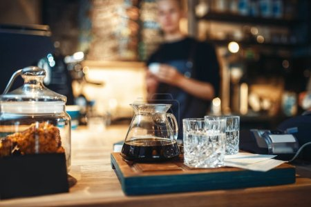 Glasses with black coffee and filtered water, male barista at cafe or bar counter on background. Professional espresso preparation by bartender in cafeteria, barman occupation