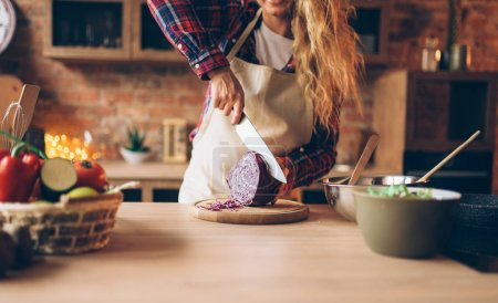 Photo for Female cook in apron cutting fresh vegetables, kitchen interior on background. Housewife with knife in hands making healthy vegetarian food, salad preparation - Royalty Free Image