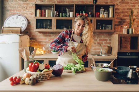 Photo for Housewife in apron prepares salad, kitchen interior on background. Female cook making healthy vegetarian food, vegetables preparation - Royalty Free Image