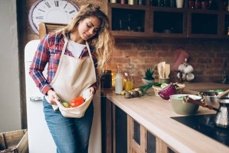 Photo for Smiling housewife keeps fresh vegetables in an apron, kitchen interior on background. Female cook making healthy vegetarian food, salad preparation - Royalty Free Image