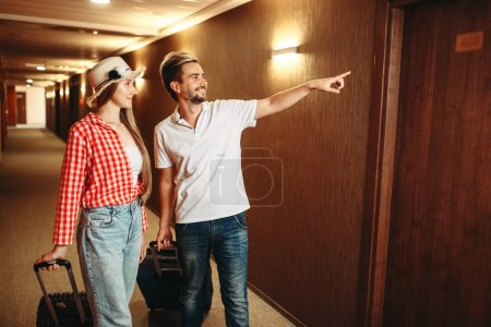 Photo pour Couple heureux avec valises à la recherche de leur chambre d'hôtel. Concept de voyage ou de tourisme, vacances d'été - image libre de droit