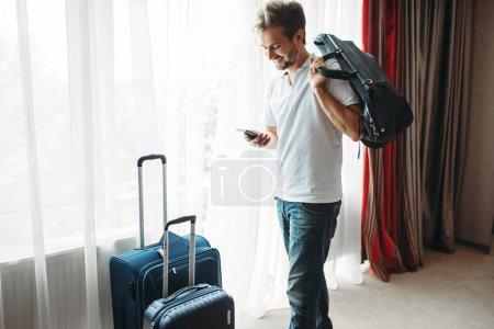 Photo pour Jeune homme avec des valises se prépare pour un voyage. Taxes sur le concept de vacances. Préparation des bagages. Voyage ou tourisme - image libre de droit