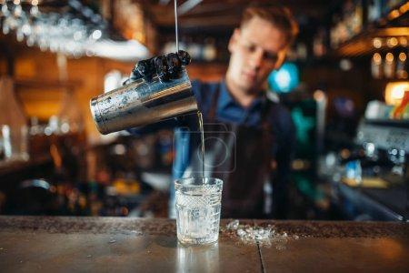 Photo pour Mâle barman en tablier verse une boisson dans un verre. Barman au bar comptoir. Préparation de boisson alcool - image libre de droit