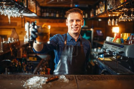 Photo for Male bartender in apron holds out a fresh alcoholic beverage at the bar counter. Barman occupation, bartending - Royalty Free Image