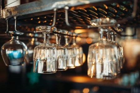 Photo for Row of glasses hanging on the bar counter closeup, nobody. Barman equipment - Royalty Free Image