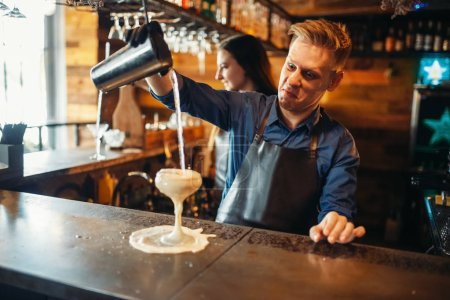 Photo for Male barman pouring the drink from the shaker at the bar counter. Alcoholic coctail preparation. Barkeeper occupation, bartending - Royalty Free Image