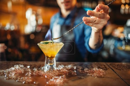 Photo for Male bartender prepares alcoholic coctail with ice. Barkeeper occupation, barman at the bar counter - Royalty Free Image