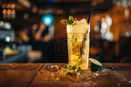 Photo pour Mojito fraîche dans un verre et de la glace sur bar comptoir closeup, personne. Feuilles de rafraîchissement d'une boisson alcoolisée au citron vert et menthe, cristaux froids sur la table - image libre de droit