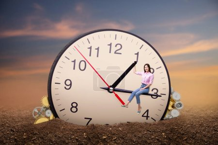 Photo for Young woman sitting on the arrow of a huge clock. Deadline concept, time does not stop - Royalty Free Image