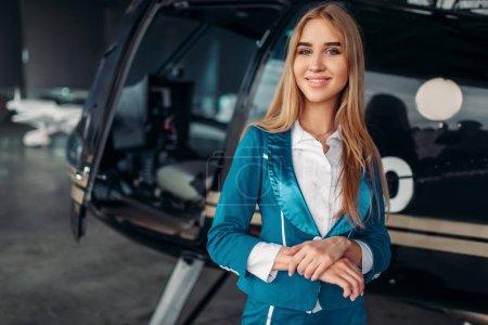 Photo pour Hôtesse de l'air en costume pose contre l'hélicoptère dans le hangar. Hôtesse de l'air en uniforme près copter. Compagnie aérienne privée - image libre de droit