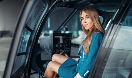 Female pilot in headphones sits in helicopter. Air hostess in uniform in copter. Private airline
