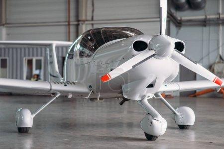 Photo pour Avion petit privé turbo-hélice dans le hangar, plane sur l'inspection avant le vol. Transport aérien, vue de face sur avion turbopropulseur - image libre de droit