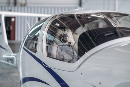 Small propeller plane in hangar, plane on inspection before flight. Private airline, air transportation, front view on turboprop airplane