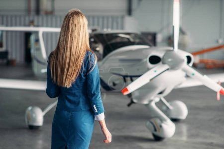 Attractive stewardess in uniform poses against turboprop airplane in hangar. Air hostess in suit near plane. Private airline, flight attendant