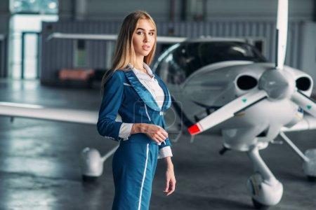 Photo pour Hôtesse de l'air attrayant dans des poses uniformes contre avion turbopropulseur dans hangar. Hôtesse de l'air en costume près plan. Compagnie aérienne privée, agent de bord - image libre de droit