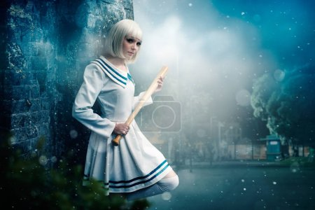 Pretty anime style blonde girl with baseball bat. Cosplay woman, asian culture, doll with wooden bit in cold tones, night city park on background