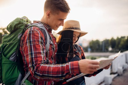Photo for Hikers with backpacks looks on map, excursion in tourist town. Summer hiking. Hike adventure of young man and woman - Royalty Free Image