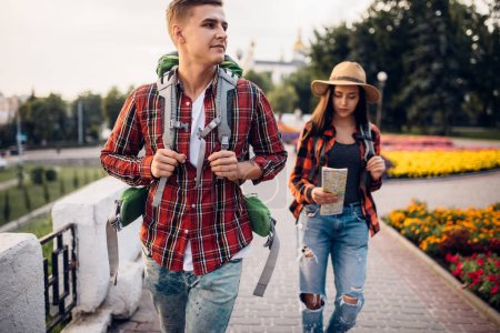 Photo for Hikers with backpacks follow the route on the map, excursion in tourist town. Summer hiking. Hike adventure of young man and woman - Royalty Free Image