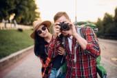 """Постер, картина, фотообои """"Туристов с рюкзаками пойти на экскурсию в туристическом городке и делает фото на память. Летом Пешие прогулки. Поход приключения молодой мужчина и женщина"""""""