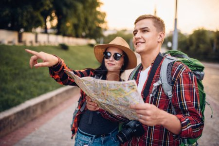 Hikers with backpacks looking for city attractions on the map, excursion in tourist town. Summer hiking. Hike adventure of young man and woman